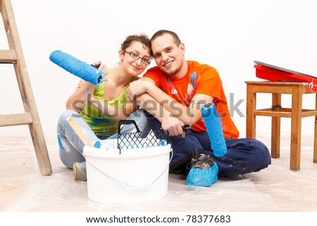 Happy young couple renovating their new home together
