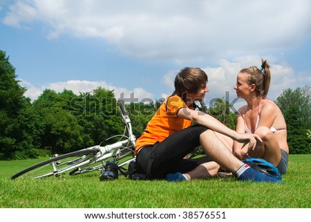 Happy young couple resting on a green meadow after bicycle trip - stock photo