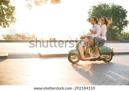 Happy young couple riding a scooter and having fun. Sun is shining in the morning - stock photo