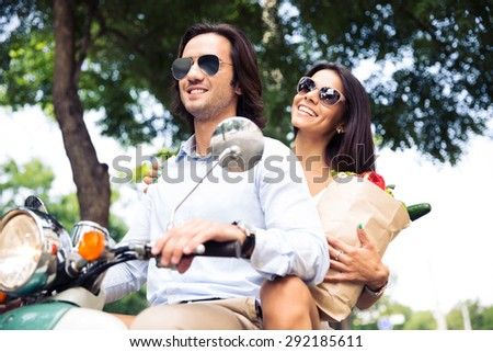 Happy young couple riding a scooter while woman holding a shopping bag full of groceries - stock photo