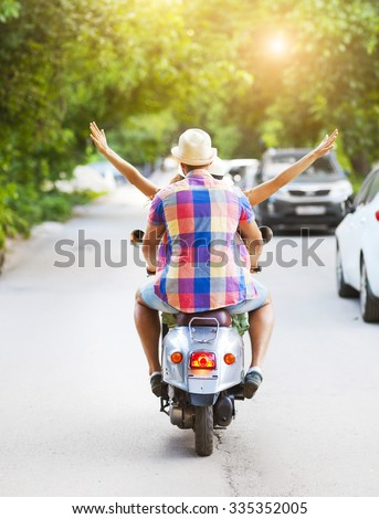 Happy young couple riding a vintage scooter in the street wearing hats. Holiday and travel concept - stock photo