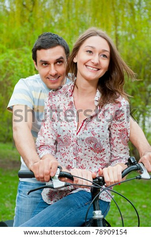 Happy young couple riding bicycle in a park
