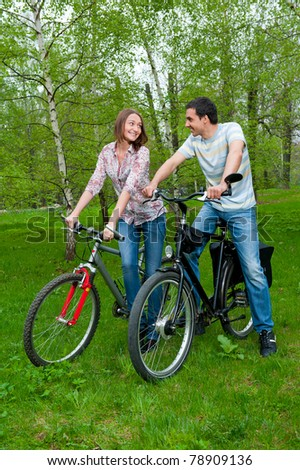 Happy young couple riding bicycles in a park