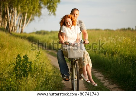Happy young couple riding on a bicycle - stock photo