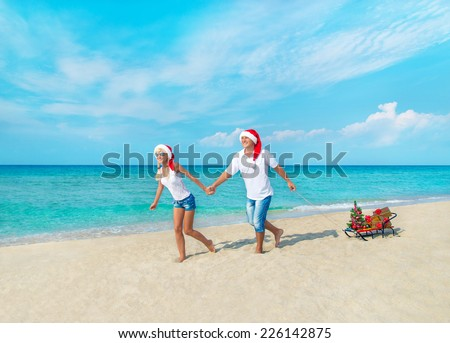Happy young couple running at sea beach in red santa hats with gifts, sled and decorated christmas tree - holiday concept - stock photo