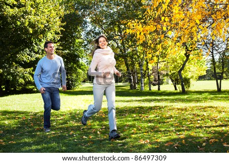 Happy young couple running at the park. - stock photo