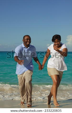 Happy young couple running on the beach.