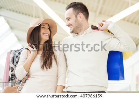 Happy young couple shopping and holding bags - stock photo
