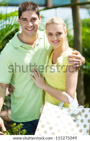 happy young couple shopping in nursery - stock photo