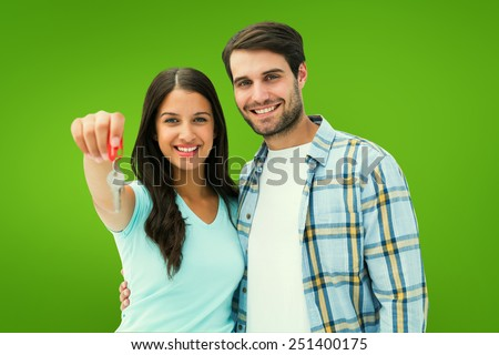 Happy young couple showing new house key against green vignette - stock photo