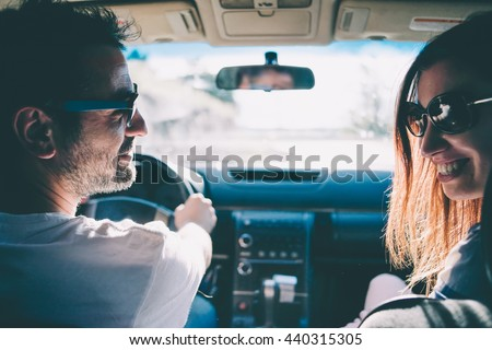 Happy young couple sit in a car. Travel and adventure concept. Toned picture - stock photo