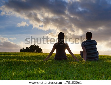 Happy young couple siting in the park during sunset - stock photo