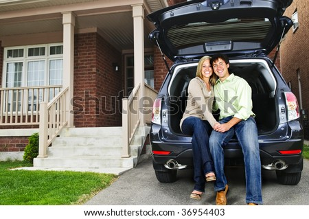 Happy young couple sitting at back of car on driveway - stock photo