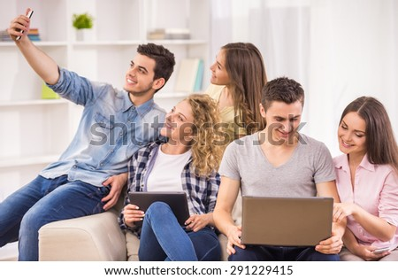 Happy young couple sitting at room and studying while their friends having fun. - stock photo
