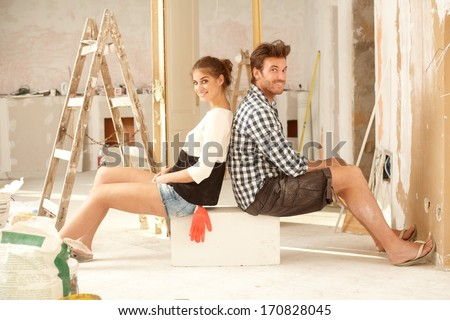Happy young couple sitting happy in home under construction.