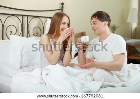 Happy young couple sitting in bed and looking at one another while drinking tea - stock photo