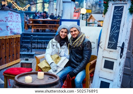 Happy young couple sitting in open air christmas fair, smiling.