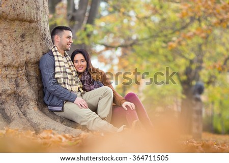 Happy young couple sitting next to the tree in a park - stock photo