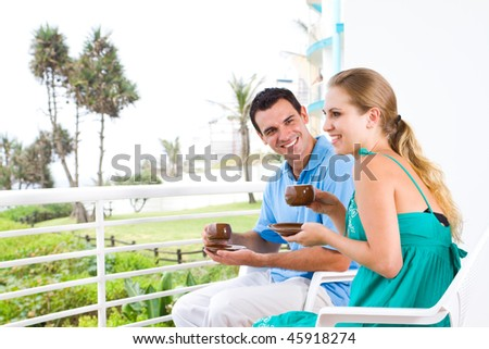happy young couple sitting on balcony drinking coffee with beautiful scenery behind