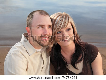 happy young couple sitting on beach with heads close - stock photo