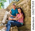 Happy young couple sitting on stairs smiling holding city map - stock photo