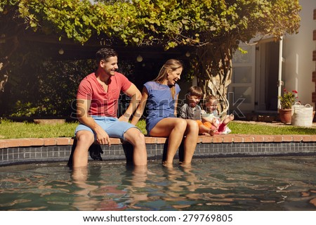 Happy young couple sitting on the edge of swimming pool with their kids enjoying a hot summer day near pool. Couple's feet in water and kids playing by outdoors. - stock photo