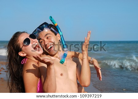Happy young couple sitting on the sand by the sea, they are happy holidays. - stock photo