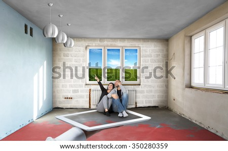 Happy young couple sitting on the tablet shows and looking up. unusual concept of buying and furnishing your new home - stock photo