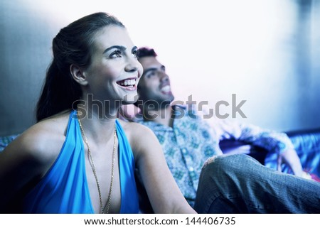 Happy young couple sitting side by side on sofa and looking up at a bar - stock photo