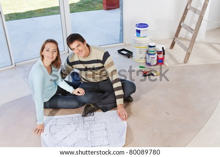 Happy young couple sitting together with blueprint and color buckets in the background - stock photo