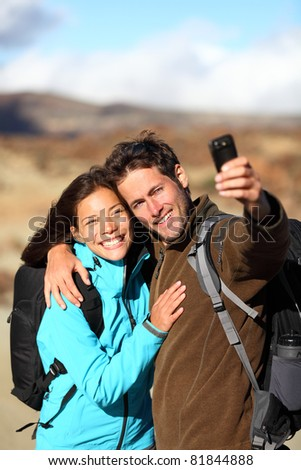 Happy young couple smiling hiking outdoors on travel taking self portrait picture with camera or mobile phone. Asian Caucasian couple on holidays. Photo from volcano Teide, Tenerife, Canary Islands - stock photo