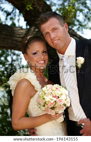 Happy young couple smiling on wedding-day, looking at camera. - stock photo