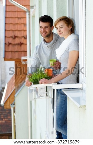 Happy young couple standing at balcony, smiling, looking away.