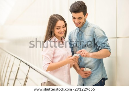Happy young couple standing at stairs and using their phones. - stock photo