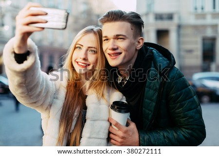 Happy young couple standing close to each other in warm coats, holding mobile phone and coffee, doing selfie and smiling, European town at background. - stock photo