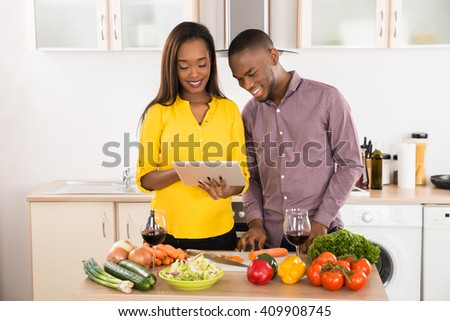 Happy Young Couple Standing In Kitchen Using Digital Tablet With Their Wineglasses