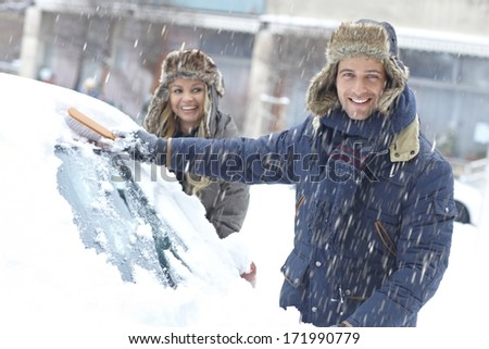 Happy young couple standing in snowfall, brushing off snow from car. - stock photo
