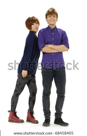 Happy young couple standing together against white background - stock photo