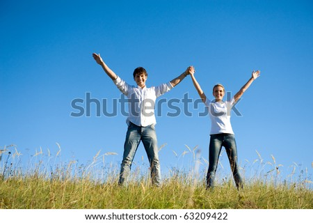 Happy young couple standing together on summer meadow with hands up - stock photo
