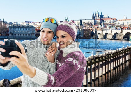Happy, young couple taking a self portrait photo, selfie in the front of  the Charles bridge in Prague, Czech Republic, Europe - stock photo