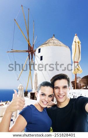 Happy, young couple taking a self portrait photo, selfie, in the front of the famous windmill in Oia, Santorini island, Greece - stock photo