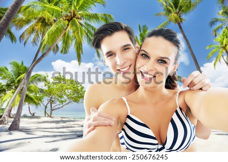 Happy, young couple taking a self portrait photo, selfie on Maldives beach - stock photo
