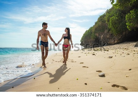Happy young couple taking a walk holding hands on the beach.  Stock image - stock photo