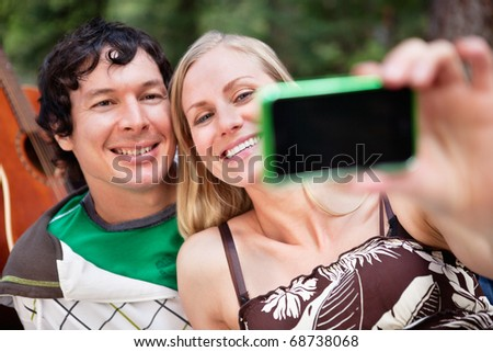 Happy young couple taking photo of themselves - stock photo