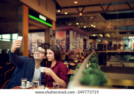 Happy young couple taking selfie with smart phone at cafe in mall. Copy space for your text. Shallow depth of field. Very useful photo for processing with one click on edit image. - stock photo
