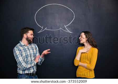 Happy young couple talking over chalkboard background with drawn empty dialogue - stock photo