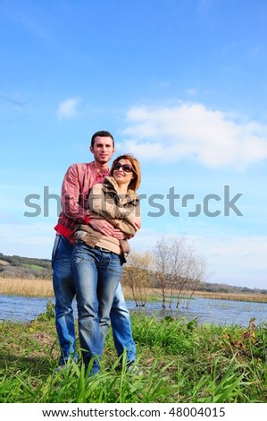happy young couple together by river on grass - stock photo