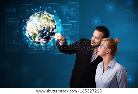 Happy young couple touching high-tech 3d earth panel - stock photo