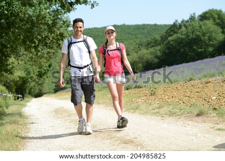happy young couple trekking together summer vacation in countryside during a sunny day - stock photo