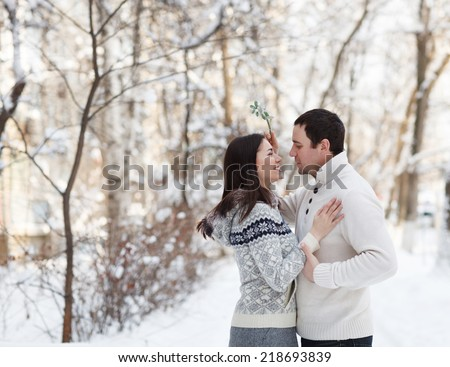 Happy young couple under mistletoe having fun in the winter park - stock photo
